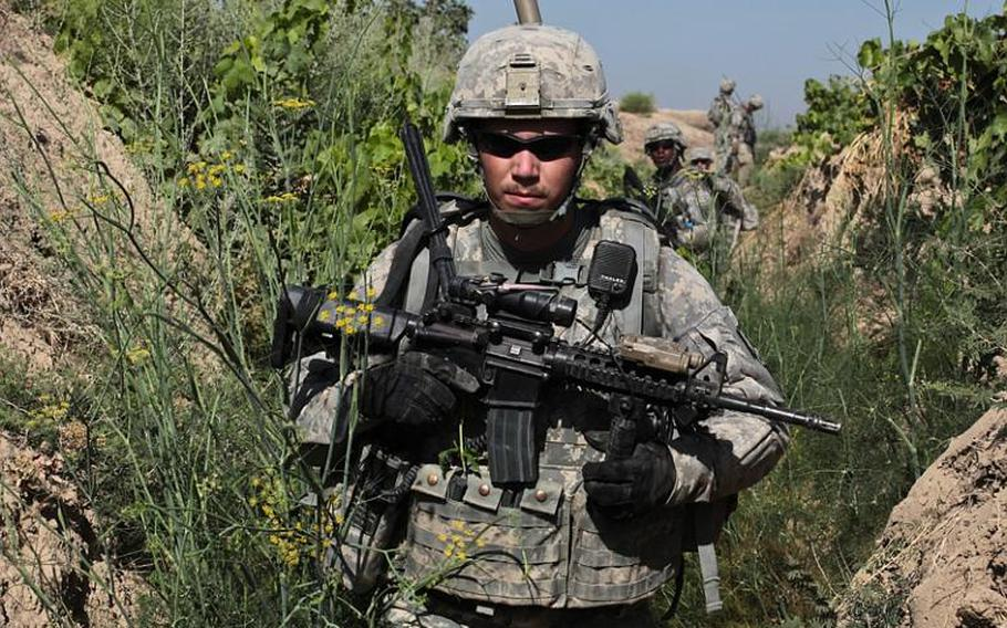 Sgt. Mitchel Stallings, of Troop B, 1st Squadron, 71st Cavalry Regiment, and other troops move through an irrigation trench in a grape orchard in Dand district, Kandahar province, Afghanistan. June 19, 2010.