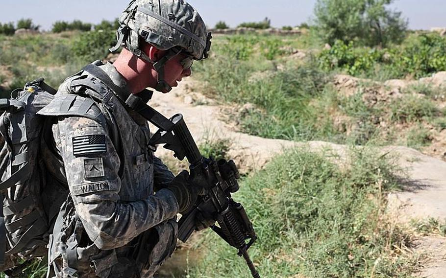 Pvt. Sean Walton, of Troop B, 1st Squadron, 71st Cavalry Regiment, keeps an eye for mines and tripwires during a patrol in Dand district, Kandahar province, Afghanistan. June 19, 2010.