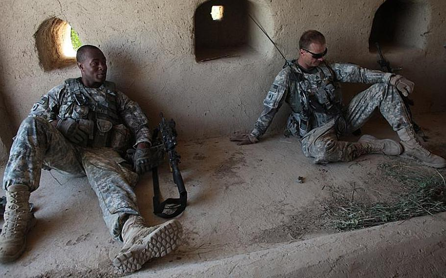 Spc. Colby Anderson, left and Staff Sgt. Richard Balch, right, of Troop B, 1st Squadron, 71st Cavalry Regiment, take a break during a patrol in Dand district, Kandahar province, Afghanistan. June 19, 2010.