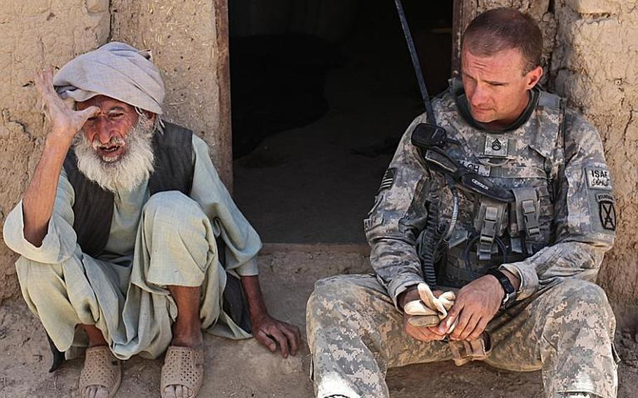"""Staff Sgt. Richard Balch, of Troop B, 1st Squadron, 71st Cavalry Regiment, listens as an old man in Dand district, Kandahar province, Afghanistan describes the hardships he has faced during the last 30 years of fighting. """"I don't need any help from anyone,"""" the old man said. """"It will only cause me problems.""""  June 19, 2010."""