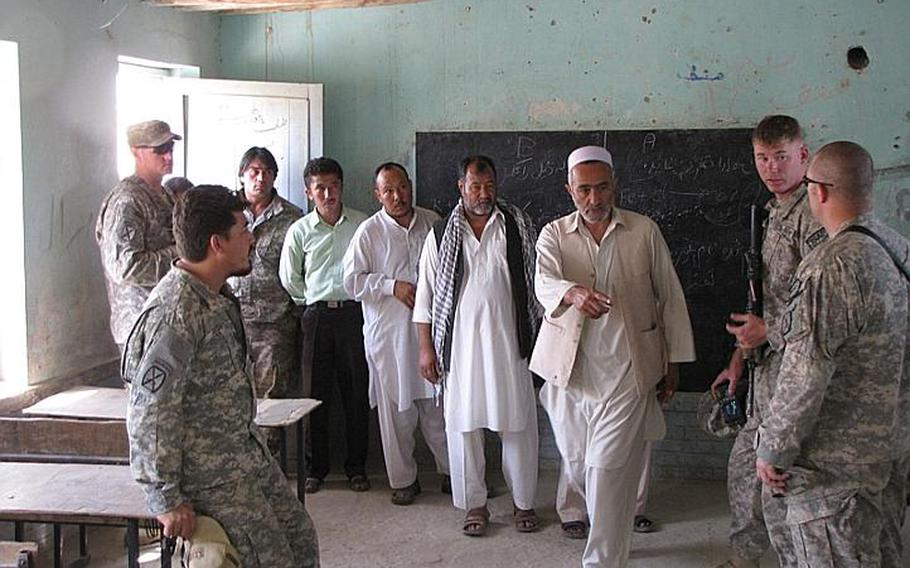An Afghan elder shows the soldiers where children sit on the floors next to the few desks that the school has.  The soldiers promised that in addition to the building projects, they would supply desks and chairs.