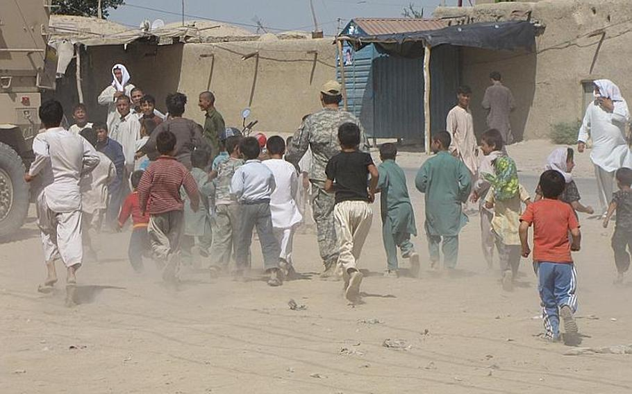 Children in the village of Marjab kick up choking clouds of talc-like sand as they race toward U.S. trucks. Word got around that the soldiers will be giving out toys.