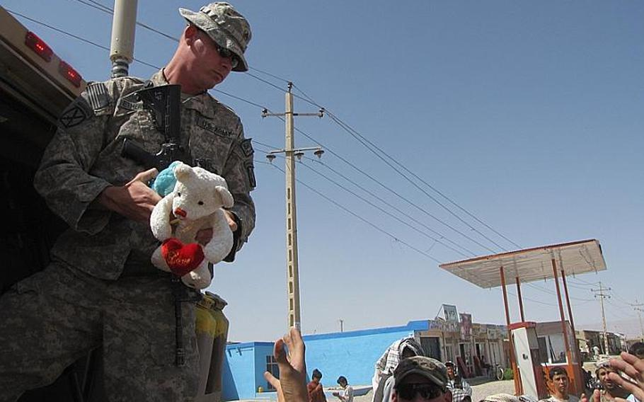 Sgt. Vernon Cole Etheridge starts to toss several toys the children of the village of Marjab.