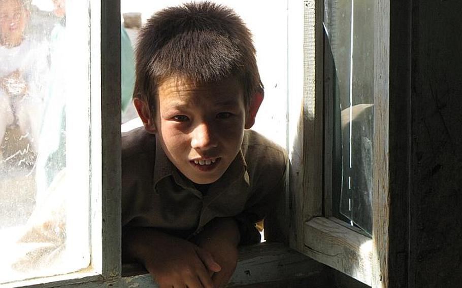 A young Marjab boy leans into a classroom window to listen as the soldiers and villagers discuss improvements.