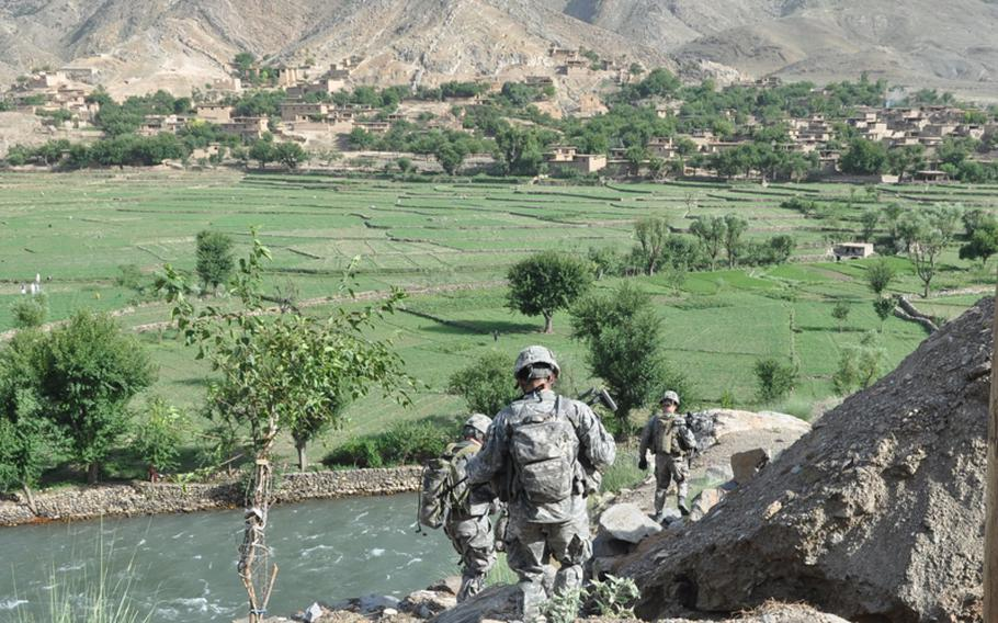 Soldiers with Company C, 1st Battalion, 327th Infantry Regiment climb down the mountainside to an overwatch position over the Pech River Valley during a visit on July 16 to the village of Qandaro.