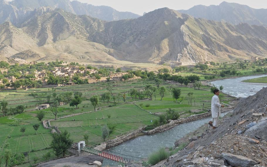 A child walks up from the valley along the Pech River in Kunar province to his home on the road above in Qandaro village on July 16.