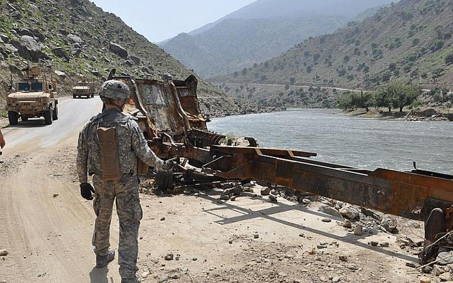 A soldier walks past the burned out shell of a supply truck on July 18 that was attacked along the Pech River Valley road right outside the abandoned Tarale police station.
