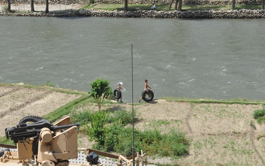 Children carry inner tubes along the Pech River on July 18 despite regular fighting nearby.