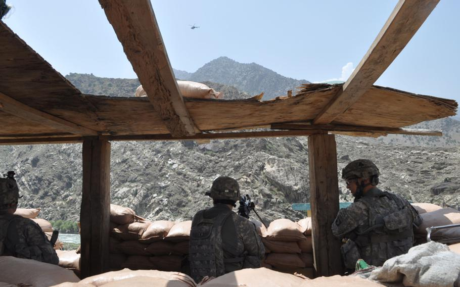 Soldiers take in the view at the guard post of the Afghan National Police station at Tantil Village in Pech River Valley of Kunar province during a visit on July 18.