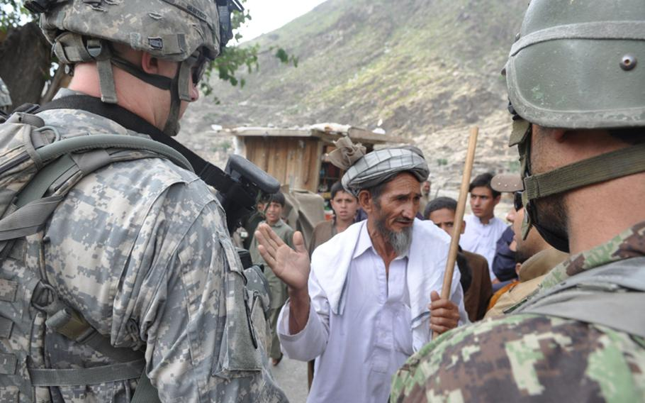 U.S and Afghan soldiers talk to a man at the Kandagal bazaar on July 20. The village is just across the Pech River from Combat Outpost Michigan.