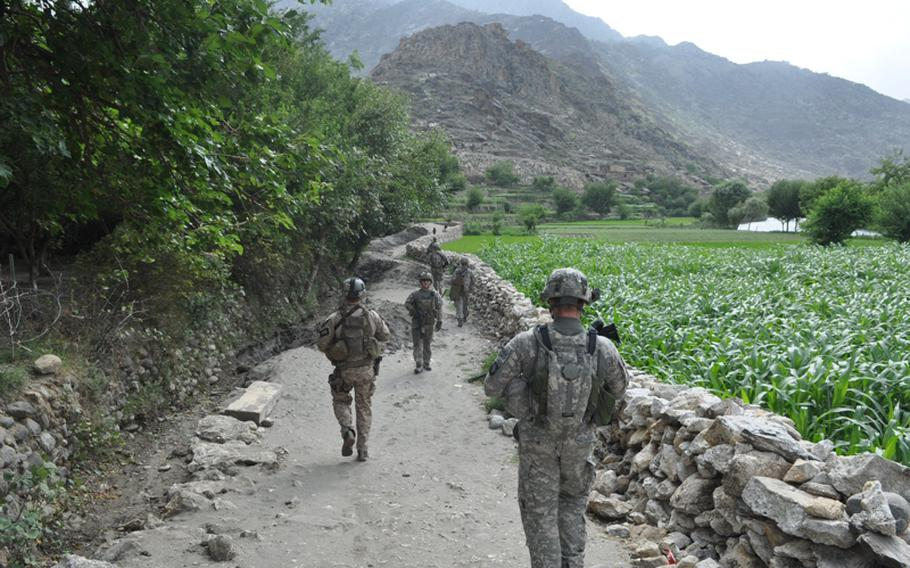 U.S. soldiers patrol the villages outside their base, Combat Outpost Michigan, on July 20, walking past tall-growing corn that soldiers have begun paying villagers not to grow. Insurgents hide amid the tall crops to shoot at Afghan and coalition forces.