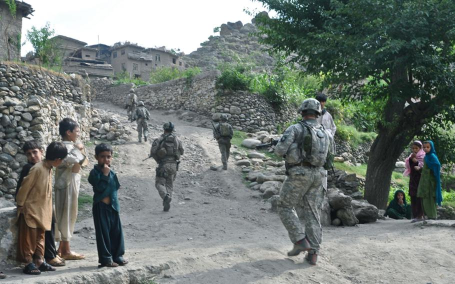 Soldiers walk through a village not far from their base, Combat Outpost Michigan, during a patrol on July 20.