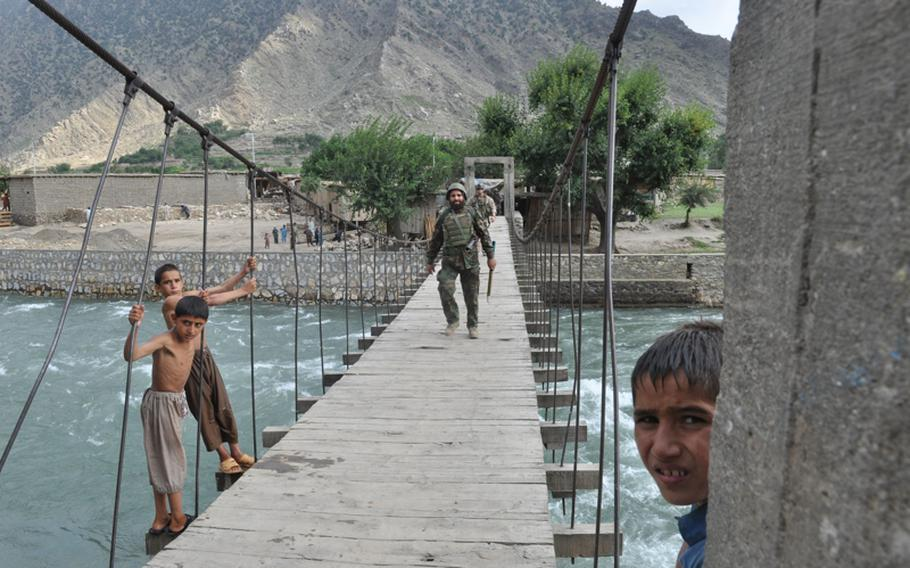 An Afghan National Army solider walks across the goat bridge over the Pech River, returning from a patrol to villages near Combat Outpost Michigan on July 20.