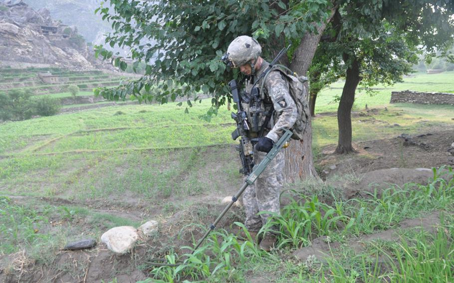 A soldier uses a metal detector on July 21 to search the fields of the hostile Chinar village at the mouth of the Korengal Valley for hidden weapons used to shoot at their outpost.