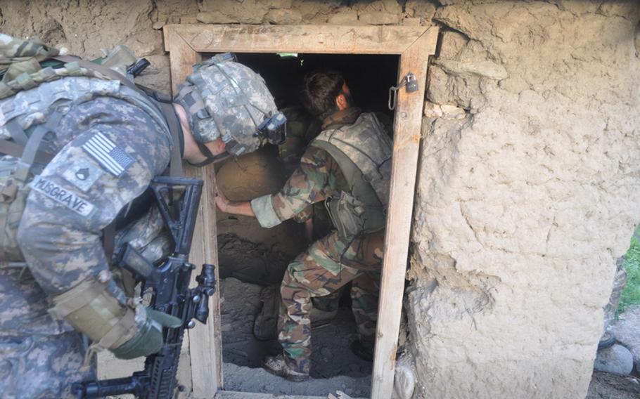 U.S. and Afghan soldiers search a field shack in Chinar village on July 21, looking for weapons used by insurgents to fire at their base from the village at the mouth of the Korengal Valley.