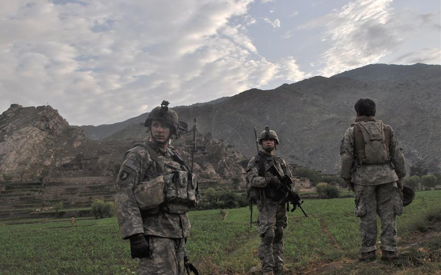 U.S. soldiers search fields in the hostile village of Chinar at the mouth of the Korengal Valley on July 21 for insurgent weapons.