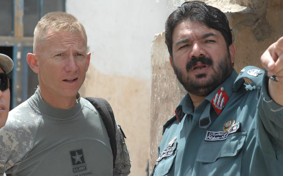 Lt. Col. Douglas Sims, left, commander of the 1st Squadron, 2nd Stryker Cavalry Regiment, meets with Gen. Juma Gul, commander of Afghan National Police in Uruzgan province, to find out why many of his men don't have AK-47 rifles.