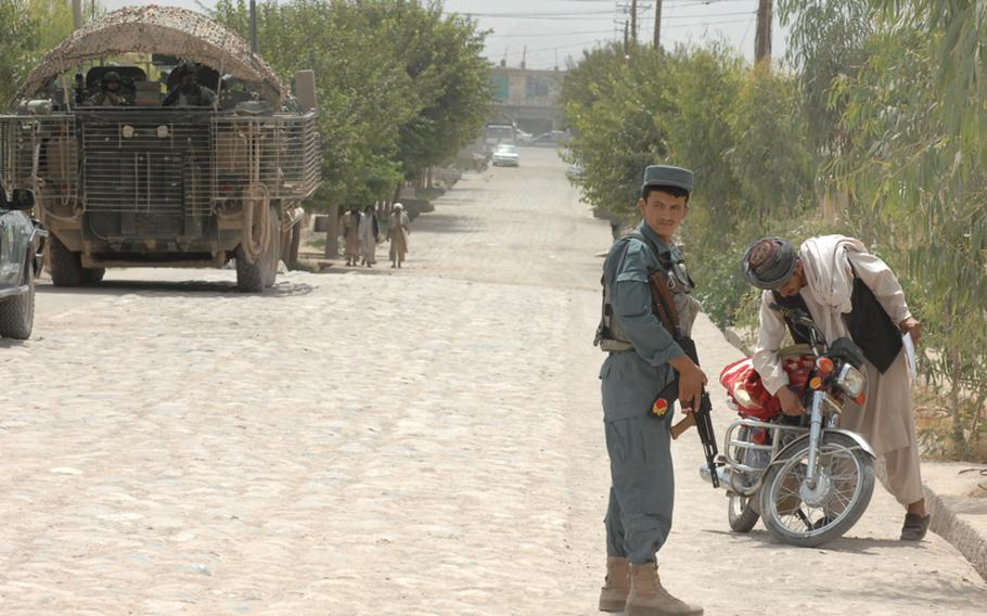 An Afghan police officer is poised to talk to a motorcyclist recently while members of 1st Squadron, 2nd Stryker Cavalry Regiment wait nearby in Tirin Kot.