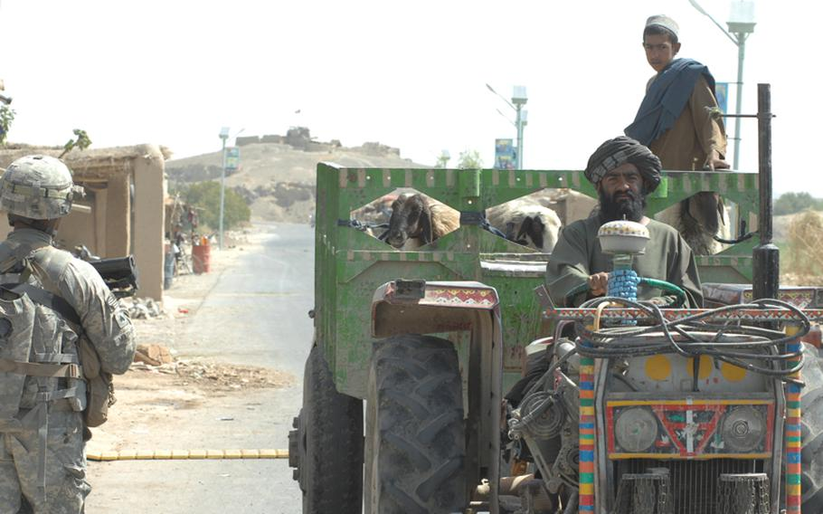 A farmer passes Sgt. Baholo Maphiri, 33, of the 2nd Stryker Cavalry Regiment. An Afghan National Police outpost watches the road at a distance.