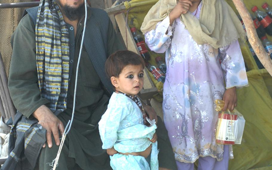 A family watches U.S. soldiers and Afghan National Police patrol in Kandahar province.