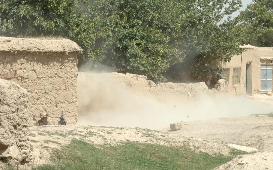 A Navy Explosive Ordinance Disposal expert, lower left, takes cover during a recent controlled denotation to remove an improvised explosive device in Helal China, Zabul province, Afghanistan.