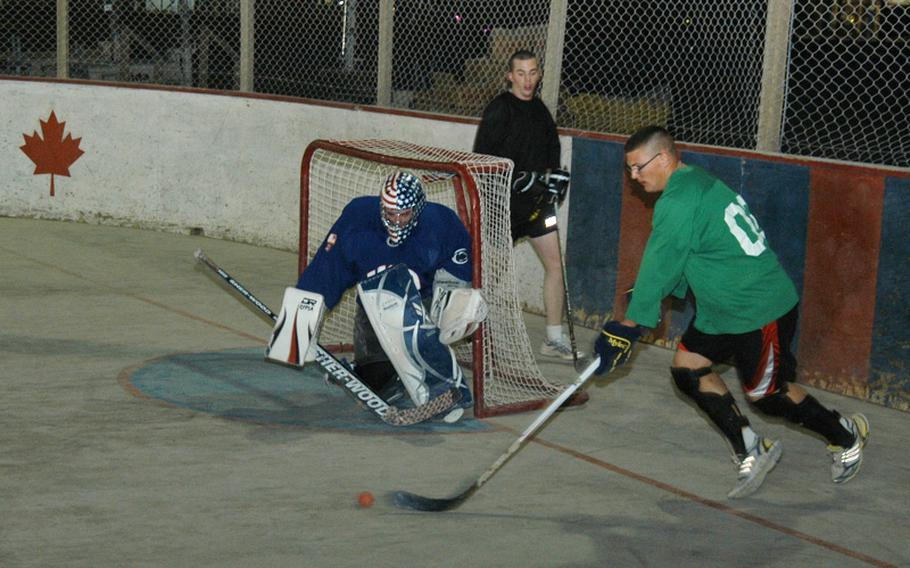 Army Capt. Ken Schoonover, the goalie, prepares to block a shot during a scrimmage of American players preparing for the upcoming ball hockey season at Kandahar Air Field in southern Afghanistan. Schoonover served as captain of the lone American team in the 24-team league last season, and wore a mask painted in an American flag design by his mother.