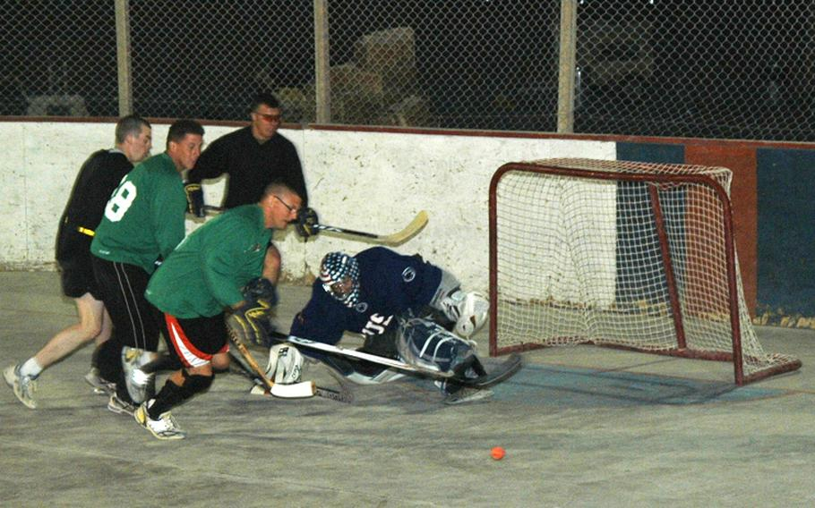 Capt. Ken Schoonover, the goalie and outgoing captain of the U.S. team in the ball hockey league at Kandahar Air Field, makes a kick save during a recent scrimmage of American players in southern Afghanistan.