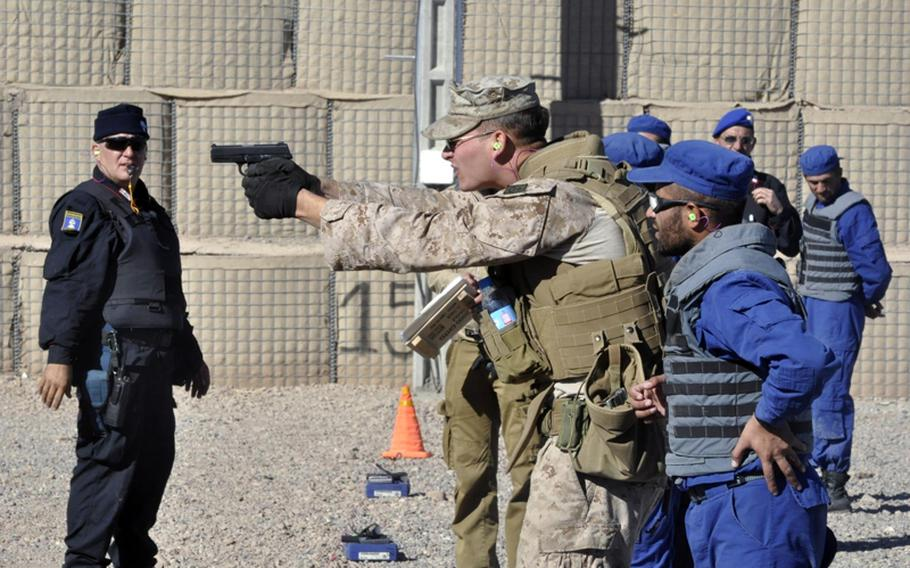ADRASKAN NATIONAL TRAINING CENTER, Afghanistan Marine Cpl. Joshua Zarr gives some pistol tips to an Afghan police recruit Nov. 7 at the Adraskan National Training Center in Afghanistan's Herat province. Zarr is a helicopter mechanic by trade but volunteered to come train the Afghans.