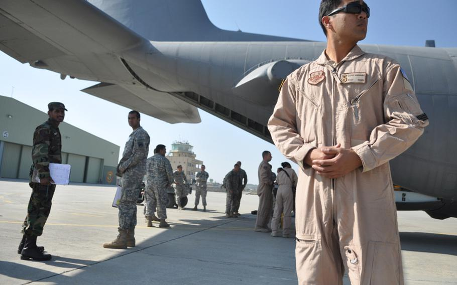 Staff Sgt. Lloyd Guerrero stands guard as a Pakistani customs inspector looks on while cargo is off-loaded from a U.S. Air Force C-130 at a small airstrip in Ghazi, Pakistan.