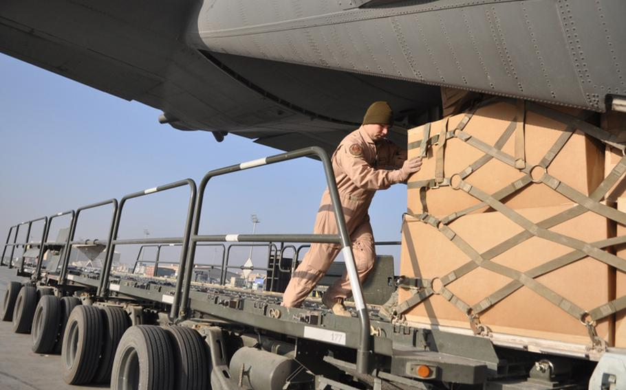 Air National Guard Staff Sgt. Anthony Legotti helps load boxes of supplies onto a C-130 cargo plane at Bagram Air Field in Afghanistan as part of the tail end of the humanitarian effort to aid flood victims in Pakistan. Legotti is a member of the Ravens, a group of specially trained troops who guard military aircraft.