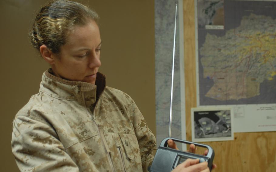 Maj. Nina D'Amato, education officer and gender adviser for Regional Command Southwest, holds a Chinese-made crank radio that ISAF troops have distributed to Afghans by the scores of thousands over the past four years. Now the command, along with RC-South, are going to air a daily radio program in Pashto to teach Afghan women to read.
