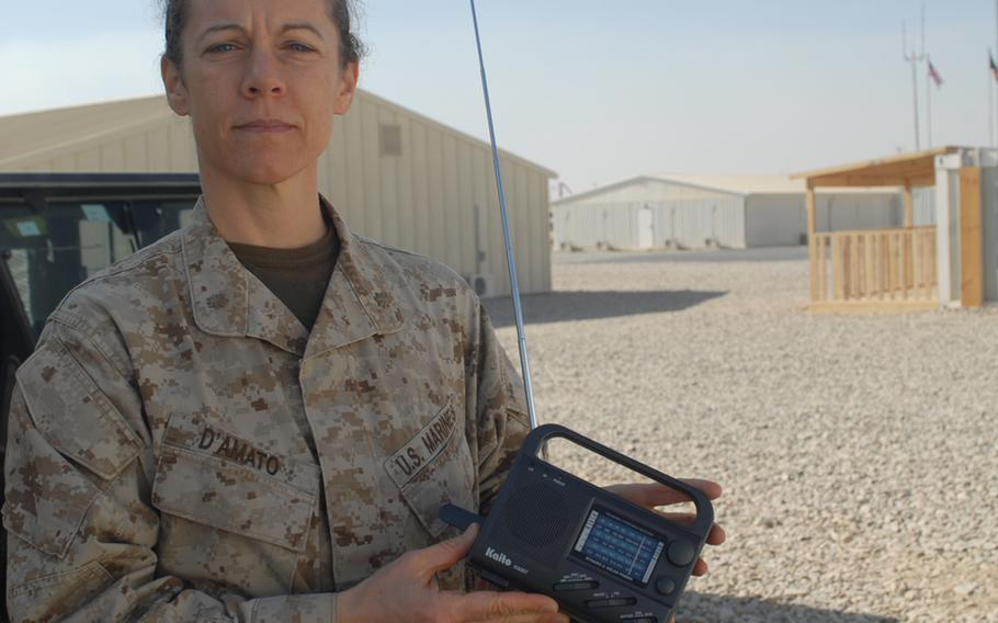 Maj. Nina D'Amato, education officer and gender adviser for Regional Command - Southwest, holds a Chinese-made crank radio that ISAF troops have distributed to Afghans by the tens of thousands over the past four years. Now the command, along with RC-South, are going to air a daily radio program in Pashto to teach Afghan women to read.