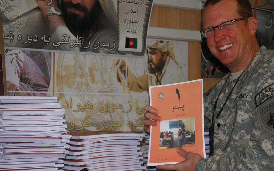 Army reservist Spc. Jim Daniels, an educator and curriculum specialist in civilian life, holds one of some 50,000 reading booklets for a radio literacy program he helped devise during his deployment with the 344th Military Information Support Operations Company (formerly known as psyops) at Kandahar Airfield. Aimed primarily at house-bound Afghan women, who have among the lowest literacy rates in the world, the effort is believed to be the first 'distance learning' program ever in Afghanistan.