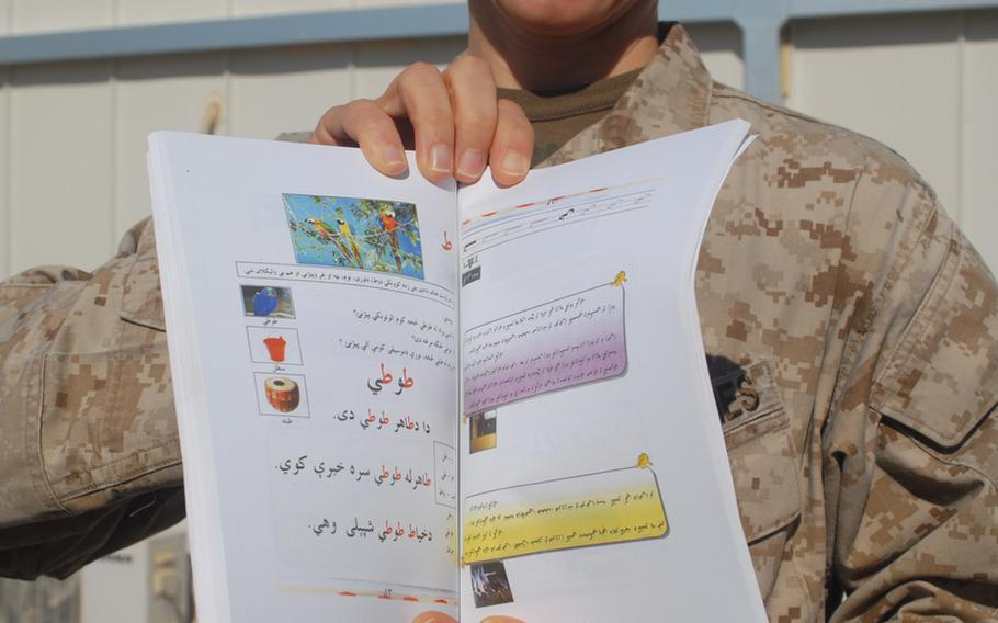 Maj. Nina D'Amato holds up one of 70,000 booklets to be distributed in rural Helmand province for women to learn to read in their homes as they listen to teachers on a daily radio program.