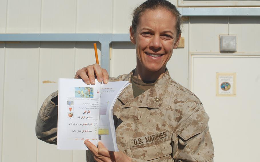 """Maj. Nina D'Amato is hoping to teach thousands of illiterate and house-bound Afghan women to read with a daily radio broadcast, a booklet and instructions on how to hold a pencil. """"If they're not going to come to us, we'll go to them,"""" she said."""