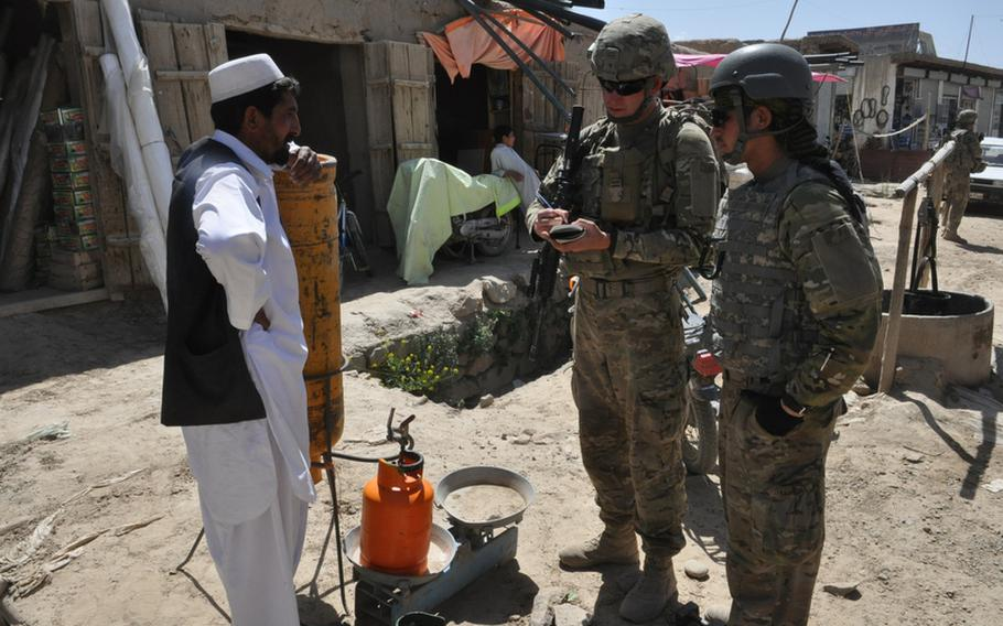 Spc. Darren Boerl, center, talks with a merchant in the Baraki Rajan bazaar in Logar province, Afghanistan, with the help of an Afghan interpreter during a recent weekday patrol.