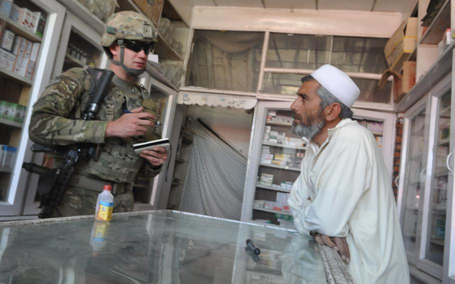 Spc. Darren Boerl chats with the owner of a pharmacy in the Baraki Rajan bazaar in Logar province, Afghanistan,  during a recent weekday patrol.