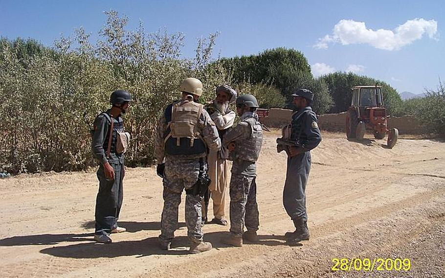 Days before he opened fire on American soldiers killing two and wounding three on Oct. 2, 2009, Said Kabeer, far right with rifle, an Afghan police officer known to the U.S. troops who trained and patrolled with him as Crazy Joe, talks with talks with U.S. and Afghan personnel.