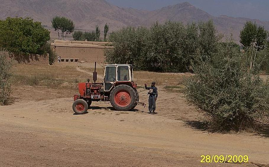 Said Kabeer, an Afghan police officer known to the U.S. troops who trained and patrolled with him as Crazy Joe, gestures at a tractor in Wardak Province, Afghanistan, days before he opened fire on American soldiers.