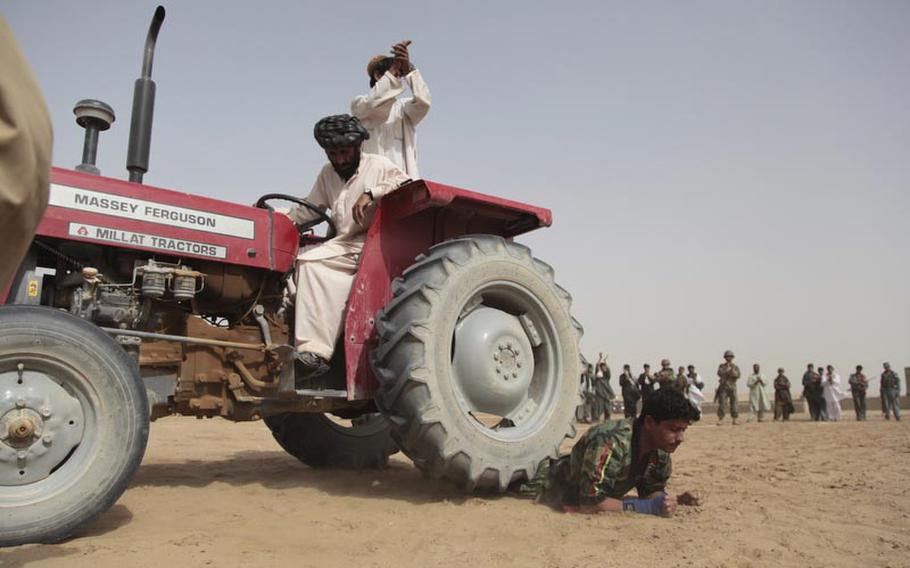 Noor Agah, 23, a karate instructor in Safar, a town near the southern end of Garmsir district in Afghanistan's Helmand province, maintains his cool as a tractor runs over his legs.