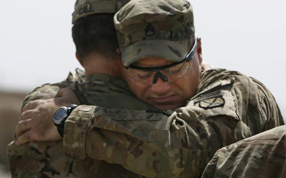 Staff Sgt. Michael Linnemeier hugs his company commander, Capt. Dennis Call, during a Saturday memorial service at Forward Operating Base Howz-e-Madad in Afghanistan. The memorial service was held in honor of five soldiers killed in an improvised explosive device attack on August 11 near Combat Outpost Nalgham.