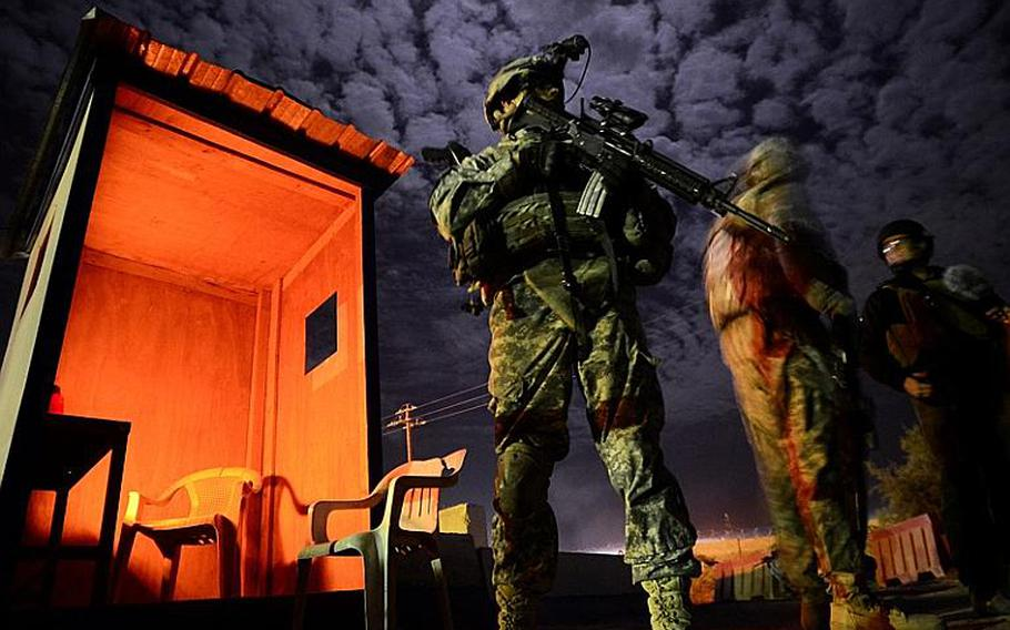 Sgt. Steven Spurrell with 2nd Battalion, 5th Cavalry Regiment, 1st Brigade, 1st Cavalry Division, stands at the ready while visiting an Iraqi police station in Tunis, Iraq, during a night patrol conducted from Contingency Operating Station Kalsu near the city of Hilla, Iraq.