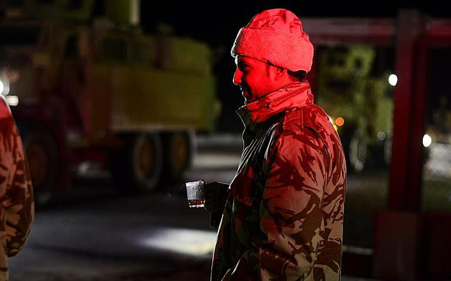 A Kuwaiti policeman drinks coffee to warm up as the first group of U.S. soldiers in the last convoy to leave Iraq drive across the Kuwait border at the Khabari crossing.