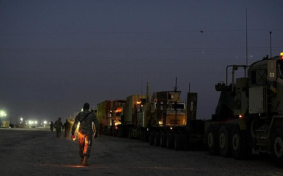 U.S. soldiers in the last convoy to leave Iraq pause to prepare to process through Kuwait customs after safely crossing the Kuwait border at the Khabari crossing.