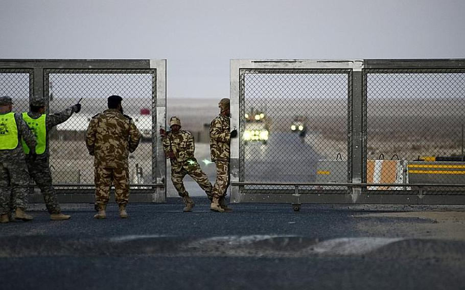 Kuwaiti policeman open the gate at the Khabari crossing ahead of a group of the last U.S. military convoy to exit Iraq.