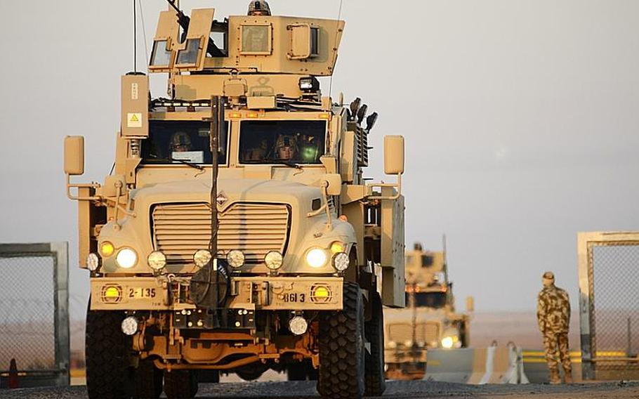 U.S. soldiers drive across the Kuwait border from Iraq at the Khabari crossing. This is the last U.S. military convoy to exit Iraq.