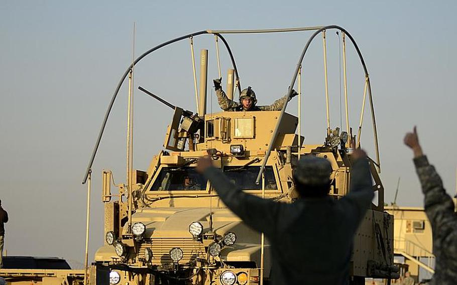 U.S. soldiers cheer for each other as the last U.S. military convoy to exit Iraq files across the Kuwait border from Iraq at the Khabari crossing on Dec. 18, 2011.