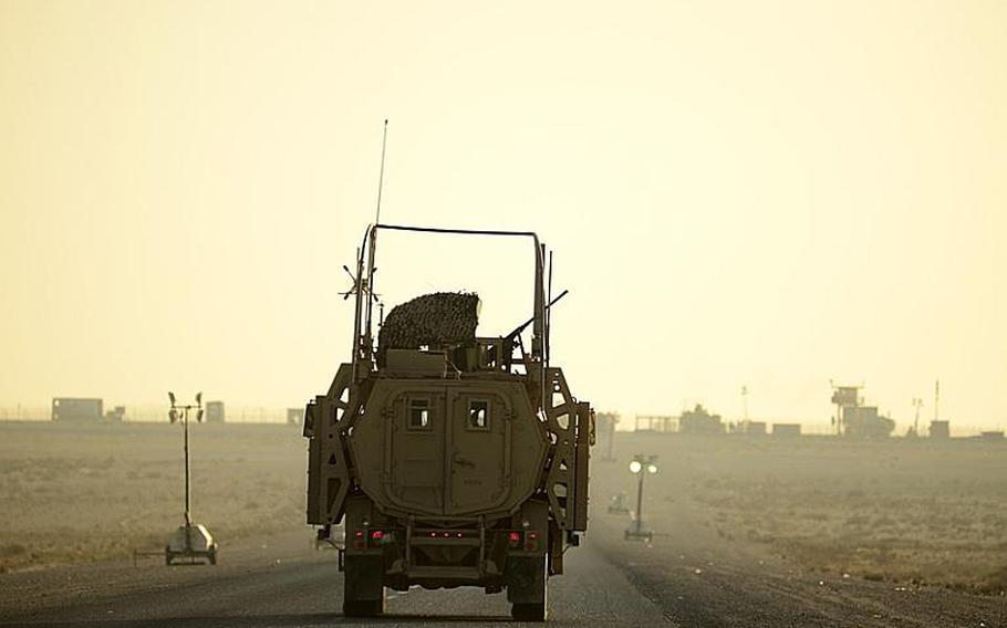 The last U.S. military vehicle to exit Iraq drives into the sunrise Dec. 18, 2011, after trailing its convoy across the Kuwait border at the Khabari crossing.