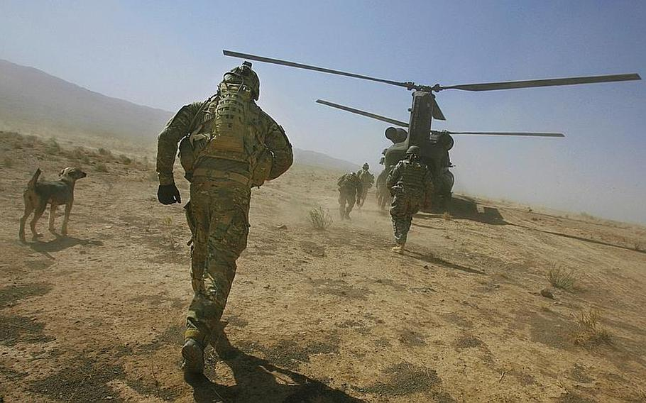 1st Lt. Weston Walrond of Company F, 4th Battalion, 101st Aviation Regiment, 159th Combat Aviation Brigade, 101st Airborne Division, runs to a Chinook helicopter following a mission in the village of Loy Shur on Sept. 23, 2011, in Zabul province, Afghanistan.