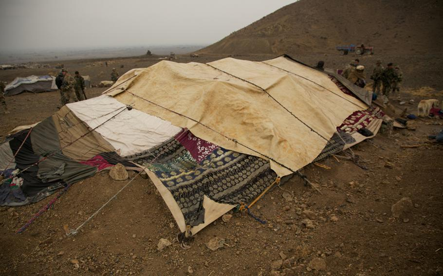 On the far side of a tent used by nomadic herdsmen, Spc. Victor Cornejo, 34, a medic from Palm Springs, Calif., examines the scalp of an Afghan woman who complained of painful lumps on her head. Afghan women are seldom seen by Western men, but Afghans make exceptions for U.S. Army medics, whom they consider doctors.